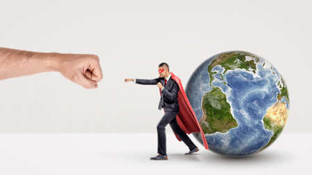 A small businessman in a red cape and a mask punching a giant fist with a small earth sphere behind him. Stock Photo