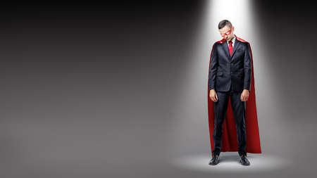 A sad businessman wearing a red superman cape standing in the spotlight with his shoulders slumped.