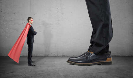 A tiny businessman in a superhero cape stands facing giant man with only his feet seen. Business competitors. Small and big companies. Monopolistic market. Stock Photo