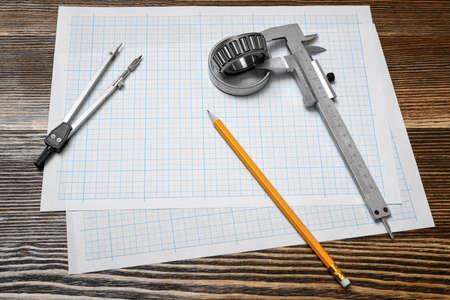 ベアリングを保持しているノギス、鉛筆とのペーパーを起草上のコンパス木製の背景。 写真素材