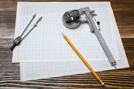 A vernier caliper holding a bearing, a pencil and a pair of compasses lying over drafting paper on wood background.
