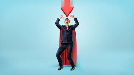 cowering: A businessman in a red cape and a mask cowering under a large red arrow pointing down at him. Stock Photo