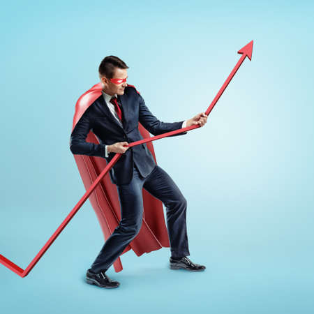 business graphics: A businessman wearing a red superhero cape trying to hold a red statistic arrow with force on blue background.