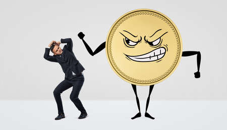 A giant humanoid coin with an angry face beating at a small businessman. Stock Photo