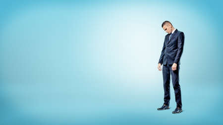 A sad businessman standing on blue background looking down with slumped shoulders. Loss and failure. Fired from work. Poverty.
