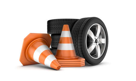 Several car wheels stacked on one another beside several orange and white traffic cones.