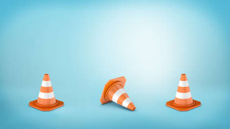 Three striped traffic cones placed on blue background and the middle one lying on its side. Stock Photo