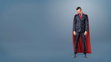 A sad businessman in a superhero red cape standing on dark blue background with his shoulders slumped.