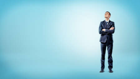 A businessman on blue background standing with hands crossed deep in thought. Stock Photo