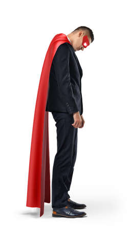 A sad businessman in a superhero red cape standing with his shoulders slumped and looking down.