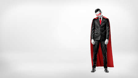 A sad businessman in a superhero red cape standing on white background with his shoulders slumped. Stock Photo