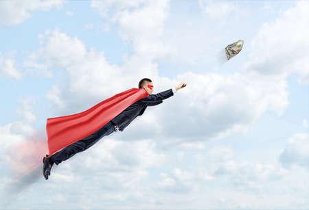 100 ドル紙幣をキャッチしようと空を飛んでいるスーパー ヒーロー マントの実業家。