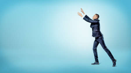 A businessman in side view with both hands raised up trying to catch something above. Reklamní fotografie