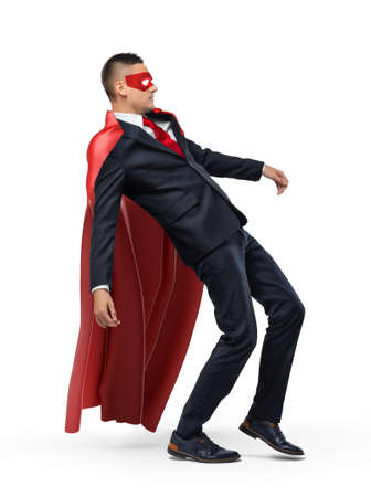 A businessman in a red superhero cape and a mask slipping and falling backwards. Stock Photo
