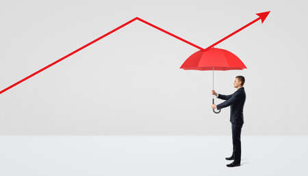 A businessman holding a red open umbrella right under a red statistic arrow pointing upwards.