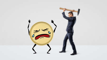 A businessman holding a large hammer over a golden coin with arms, legs and a crying face.