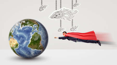 A small businessman in a superhero cape flying towards a tiny earth globe with white paper comets hanging above him. Stock Photo