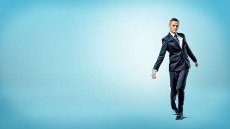 A businessman on blue background walking on unsteady legs like a broken doll. Stock Photo