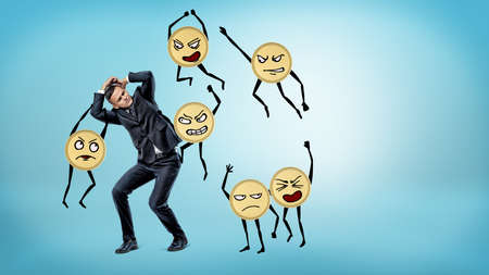 A scared businessman standing and hiding his face and body from many humanoid golden coins beating him. Stock Photo