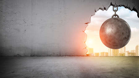 A black wrecking ball hanging inside the opening in a concrete wall showing city landscape.