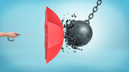 A male hand holding an open red umbrella which protects from a collision with a broken wrecking ball.