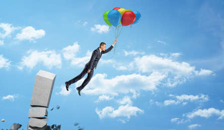 A businessman holding a set of colorful balloons on a string and flying away from a crumbling concrete column.