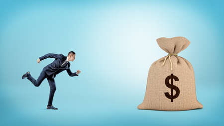 A small businessman running to a giant closed sack with a dollar sign on it. Stock Photo