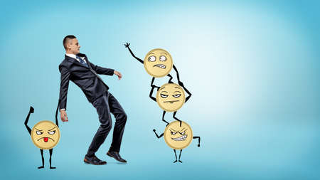 A businessman losing his balance while many large golden coins with arms and legs are trying to make him fall.
