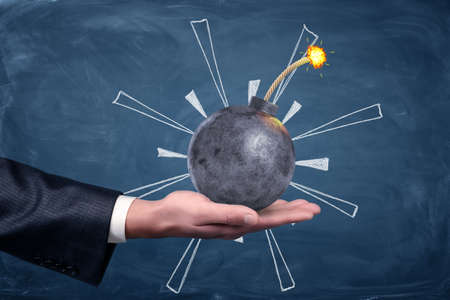 un mâle main tenant une bombe en métal rond avec un fusible allumé sur fond tableau noir .