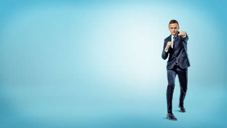 A serious businessman in front view throwing punches while standing on blue background.