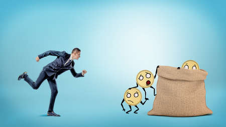 A small businessman running to a large full sack where many coins with arms and legs are getting in. Stock Photo