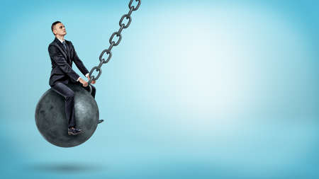 A businessman swinging on a large wrecking ball and looking up on blue background.