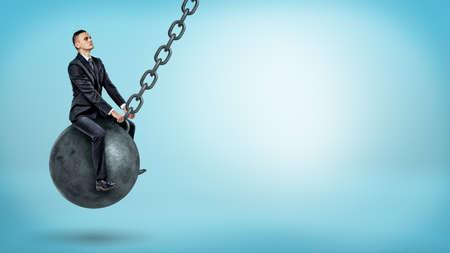 Un hombre de negocios que se balancea en una bola que arruina grande y que mira para arriba en fondo azul. Foto de archivo