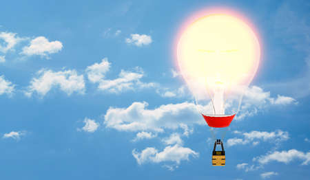 A hot air balloon with an incandescent bulb in place of its envelope on cloudy sky background. Stock Photo