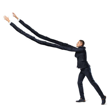 A businessman on white background in side view with extremely long arms trying to grab something above.