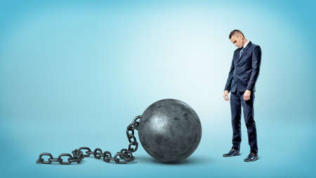 A small sad businessman looking down to a giant iron ball and chain on blue background.