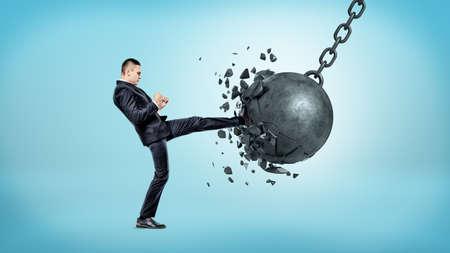 Un hombre de negocios en el fondo azul que golpea con el pie en una bola que arruina y que se estrella con muchos pedazos que vuelan lejos. Foto de archivo - 81162047