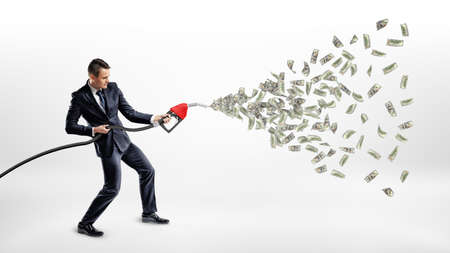 Ein lächelnder Geschäftsmann, der eine Gasdüse hält, während viele Dollarscheine von ihm anstelle von Benzin fliegen. Standard-Bild