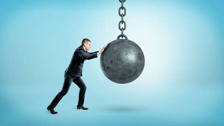 A businessman on blue background pushing at a hanging unmoving wrecking ball.