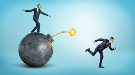 A businessman standing on a black round bomb with a lit fuse beside a man running away from it. Stock Photo