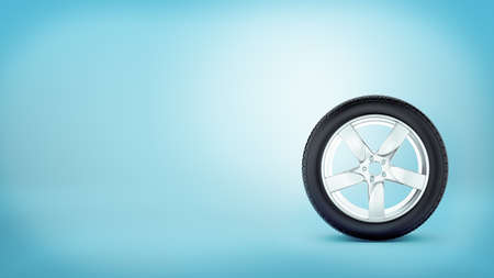 A car wheel with five spokes standing on the tire rim on blue background.