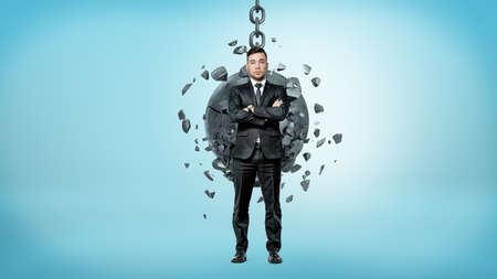 A businessman looking up over his shoulder white a wrecking ball crashes on his back. Stock Photo