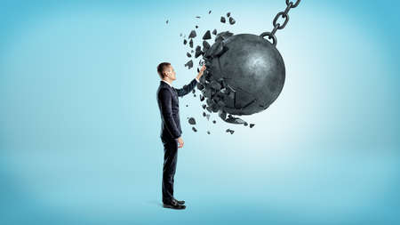 A businessman on blue background touching a wrecking ball when it crashes under his hand.
