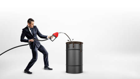 A businessman holds a gas nozzle and overfills a black barrel with oil. Stock Photo