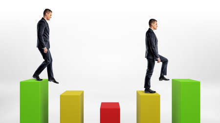Two businessmen on white background stepping up and down green, yellow and green statistic columns. Stock Photo