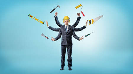 A businessman with many hands that wears a hardhat surrounded by construction instruments. Stock Photo