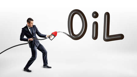 A businessman holds a gas nozzle and writes a large word Oil on white background.
