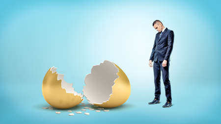 A sad businessman on blue background looks down on a giant broken golden egg. Stock Photo