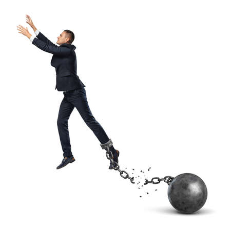 heavy risk: A businessman leaping away from an attached iron ball with a broken chain.