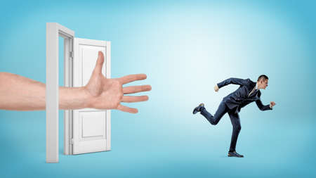 A giant open hand tries to catch a small running businessman through an open white door. Stock Photo